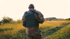 Close up of military's shoulder with automaton goes in the fields - stock footage