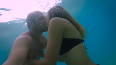 Sweet couple kissing under the water in the ocean (slow motion) Stock Footage