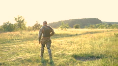 Military man with automaton go away in the steppe. Slowly - stock footage