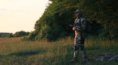 Tired soldier with automaton in hands goes on the path. Slowly Stock Footage