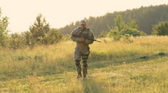 Military man with automaton in hands goes on the path. Slowly - stock footage