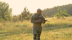 Tired soldier with automaton in hands goes on the path. Slowly - stock footage