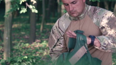 Close up of warrior wears body armor in the forest. Slow motion - stock footage