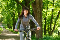 Cyclist woman riding a bicycle in park Stock Photos