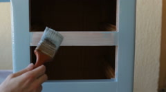 Hand with paintbrush painting wooden furniture using light blue paint Stock Footage
