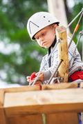 Little serious boy attaches safety cords on the rope track Stock Photos