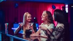 Three beautiful girls at bar in nightclub - stock footage