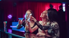 Three beautiful girls at bar in nightclub Stock Footage