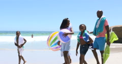 4K Happy family having fun at the beach, walking & carrying beach equipment Stock Footage