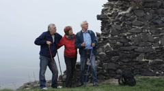 Senior men and woman with trekking poles talking outdoors on hiking trip. Stock Footage