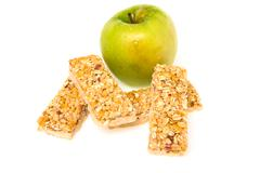Muesli bars dried fruit on isolated background with apple Stock Photos