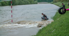 Two guys with rubber rings are going into water Stock Footage