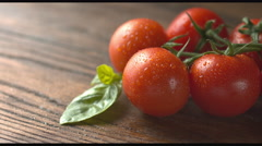 Red tomatoes with basil on wood Stock Footage