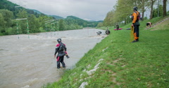 Two security men are standing in the water and on the river bank - stock footage