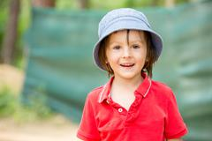 Portrait of a cute little boy in amusement park, having fun - stock photo