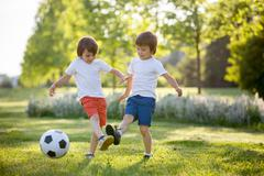 Two cute little kids, playing football together, summertime. Children playing Stock Photos
