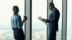 Young businesspeople standing with newspaper and coffee by window in the office Stock Footage