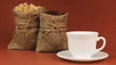 Coffee is poured into a cup and behind stands coffee beans in burlap bag and - stock footage