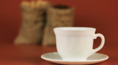 Cup of coffee. Behind stands coffee beans in burlap bag and next sugar in burlap Stock Footage