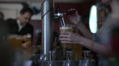 Female Bartender Serving Pints Of Beer To Crowd In The Bar Stock Footage