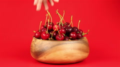 A man's hand take red ripe cherries in wooden bowl on red background - stock footage