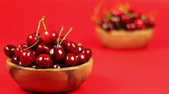 Two wooden bowls of cherries on red background - stock footage