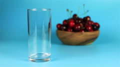 Red cherry juice being poured in a glass and red ripe cherries in wooden bowl on Stock Footage