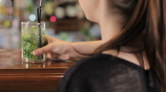 Young woman drinks mojito. Shot from behind Stock Footage