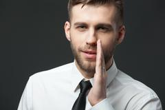 Young businessman whispering trade secrets on dark gray background. Stock Photos