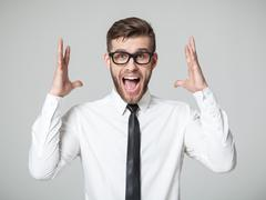 Young businessman screaming at camera isolated. Stock Photos