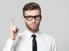 Handsome businessman showing his index finger up. - stock photo
