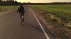 Person rides a sports bicycle on asphalt and gives a sign that turns on the left Stock Footage