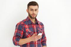Handsome young man in casual wear typing text message. - stock photo