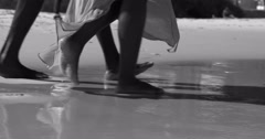 4K Low angle view, the feet of couple walking on beautiful tropical beach Stock Footage