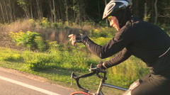Camera shoots a man who goes on a sports bike waving his hand forward Stock Footage