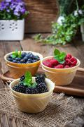 Blackberries, raspberries and blueberries in a waffle bowls. - stock photo