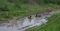 Two men are trying to swim in a big mud pool Stock Footage