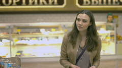 Sweet young woman walking on the supermarket Stock Footage