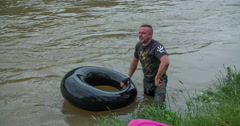 A man starts swimming in the river with a rubber ring Arkistovideo