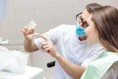 Man dentist show dentures teeth at dental surgery to patient - stock photo