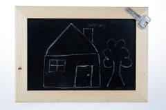 Funny sketch of house with tree and key on blackboard Stock Photos
