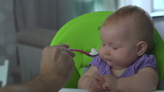 Baby refuses to eat. Dad feeding the baby girl - stock footage
