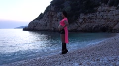 High heeled pregnant on the beach at sunset 2 Stock Footage