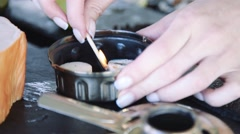 Girl lights the dry fuel by matches for cooking Stock Footage