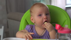Baby sitting on chair and eats Stock Footage