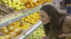 Cute girl standing near the shelves with fruits in the supermarket Stock Footage