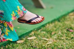 Woman foot with nail polish wearing flip-flop Stock Photos