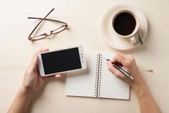 Small notebook and coffee cup Stock Photos