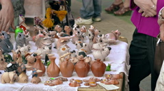 Buyers Consider Souvenirs Hand-Made of Clay in Stall in Open Air Stock Footage