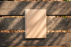 Notepad on wood table - stock photo